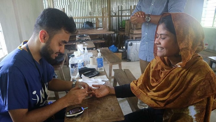 Maa volunteer, Tanvir, measures an expectant mother's blood sugar levels at a health camp in Bangladesh this summer.
